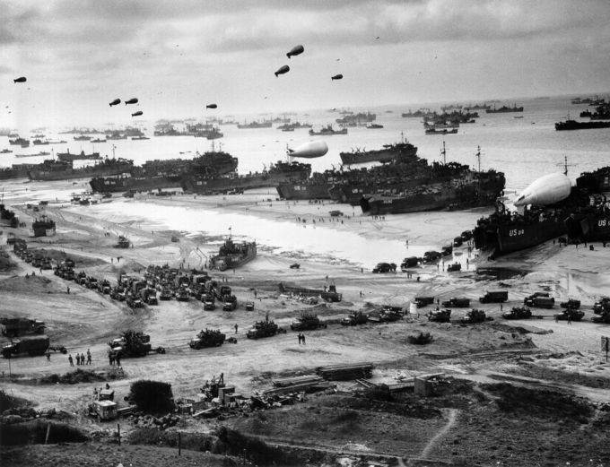 A photo of the Normandy landings, with about a dozen landing boats deploying soldiers and trucks, hundreds of battle ships farther out into the water, and the beaches covered in military trucks and equipment.