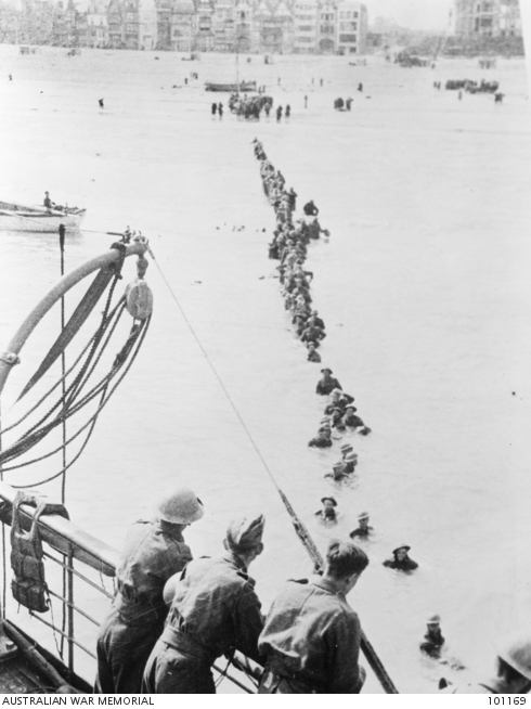 Photo of British troops on a ship bringing French troops aboard, who are lined up in the water.