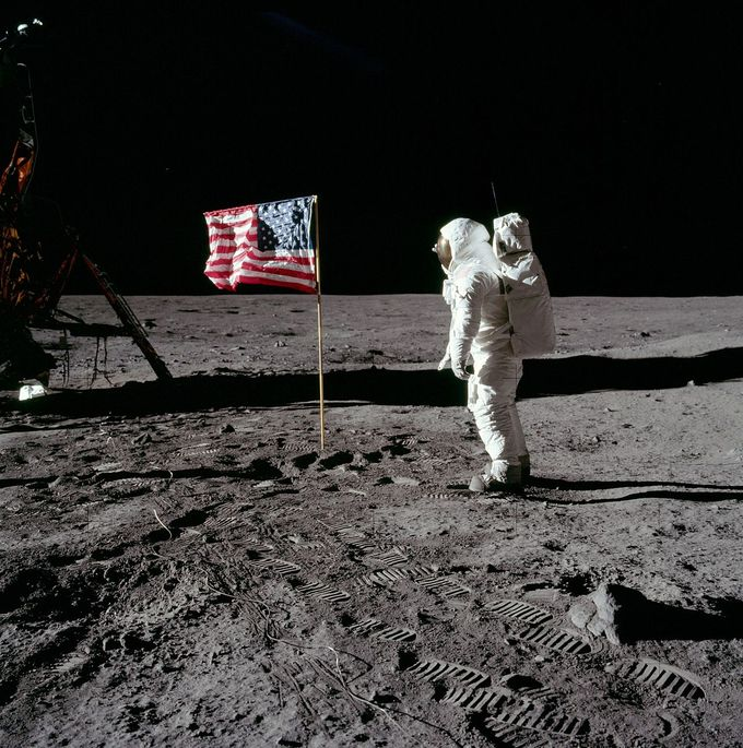 Photo of Buzz Aldrin on the Moon during the Apollo 11 landing. The photo shows him on the surface of the moon, with an American flag in front of him.