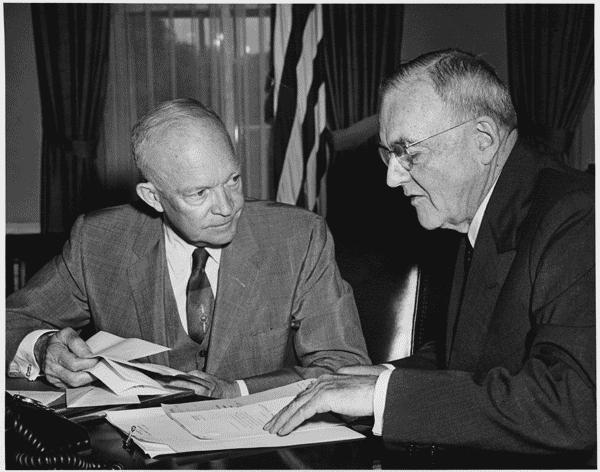 A photo of Secretary of State John Foster Dulles, right, shown here with President Eisenhower in 1956, sitting at a desk looking over papers.