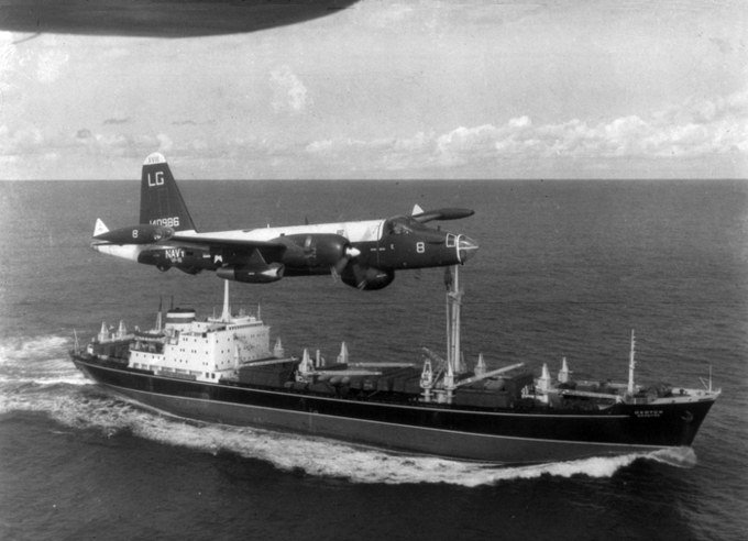 A U.S. Navy P-2H Neptune of VP-18 flying over a Soviet cargo ship with crated Il-28s on deck during the Cuban Crisis.