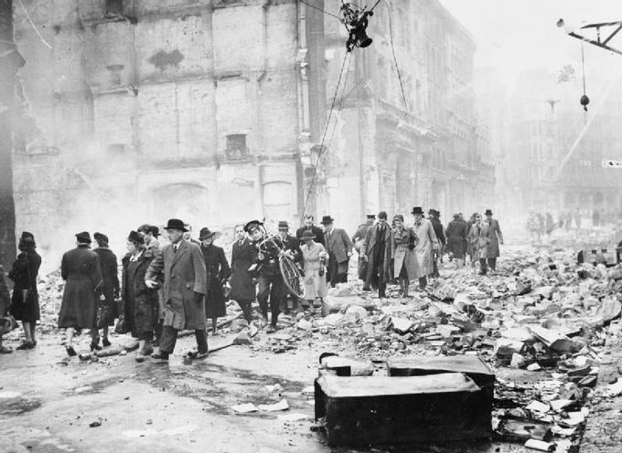 Photo of British citizens walking to work through rubble caused by German air raids.