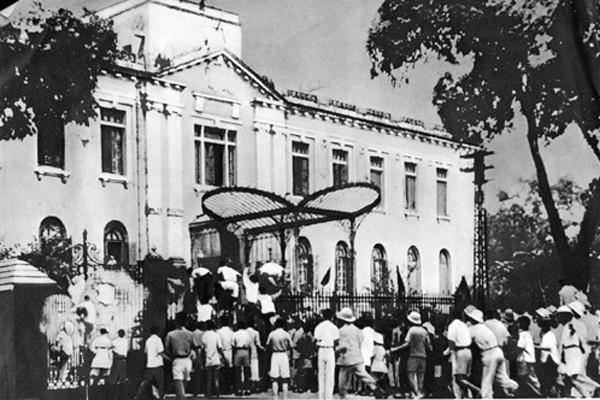 A fotografia mostra uma multidão reunida nos portões de um prédio do governo.