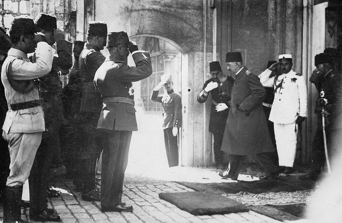 Photo of Mehmed VI, the last Sultan of the Ottoman Empire, leaving the country after the abolition of the Ottoman sultanate, 17 November 1922. He is walking through an archway surrounded by saluting soldiers.
