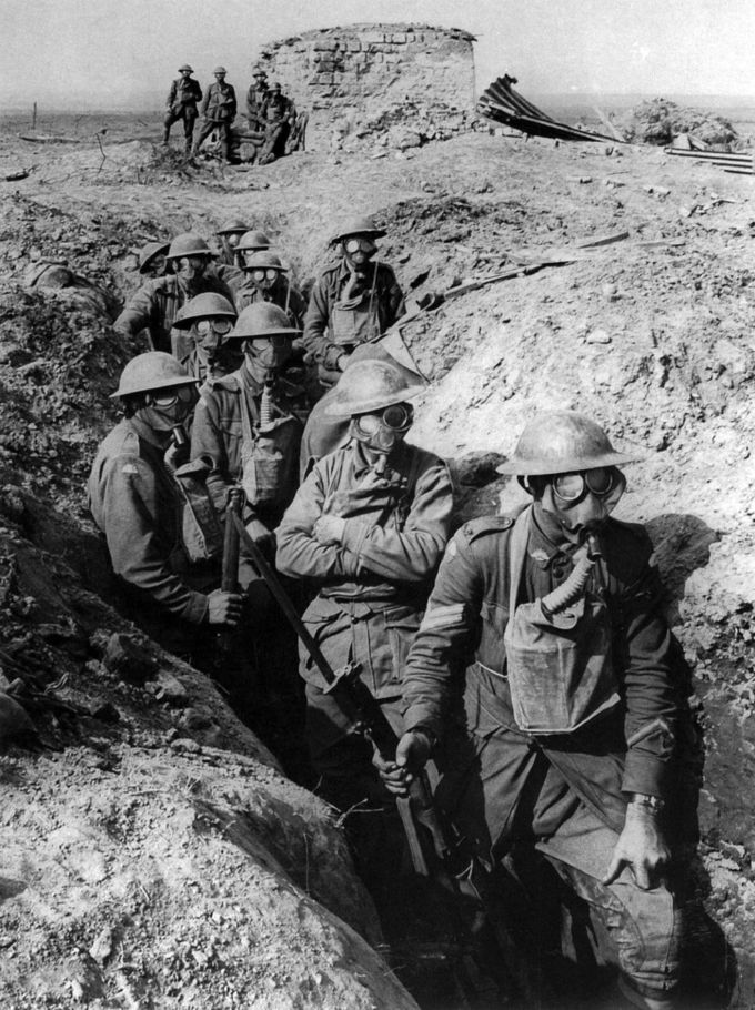 Australian infantry with gas masks in a trench.