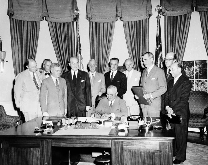Photo of U.S. President Harry S. Truman signing the North Atlantic Treaty seated at the desk in the Oval Office with eleven men standing behind him.
