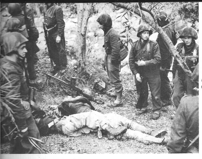 A photo of several French solders standing around the dead bodies of Algerian rebels.