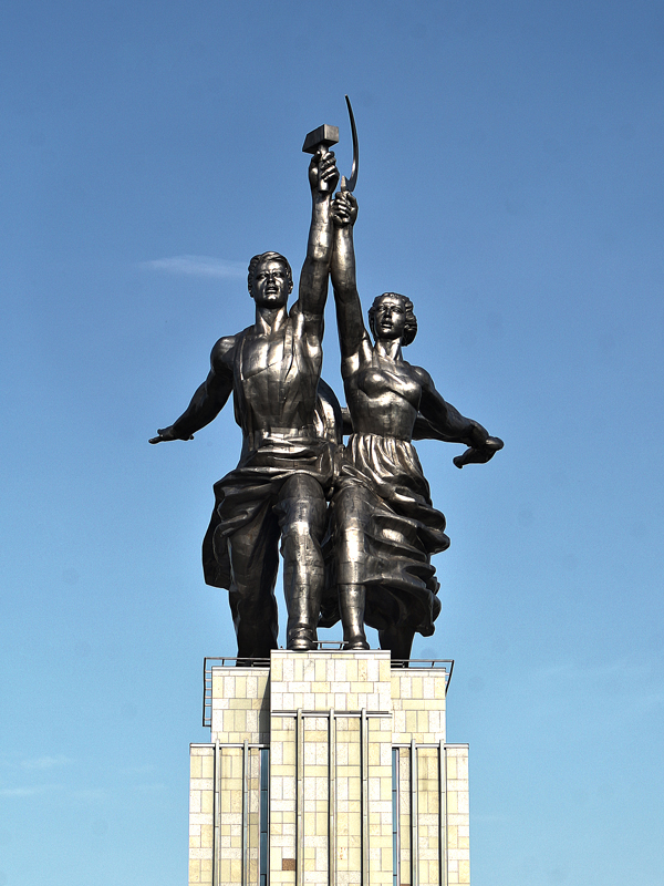 A photo of a Soviet era statue characteristic of socialist realism, depicting a male worker holding a hammer aloft in his hand and a woman worker with a sickle aloft in her hand.