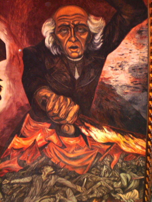The expressionistic painting depicts Miguel Hidalgo y Costilla holding his left hand above his head and his right hand waving a red flag. He stands atop a group of men also waving red flags.