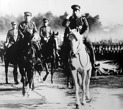 Emperor Shōwa riding his stallion Shirayuki alongside other military officers riding horses during an Army inspection, August 1938.