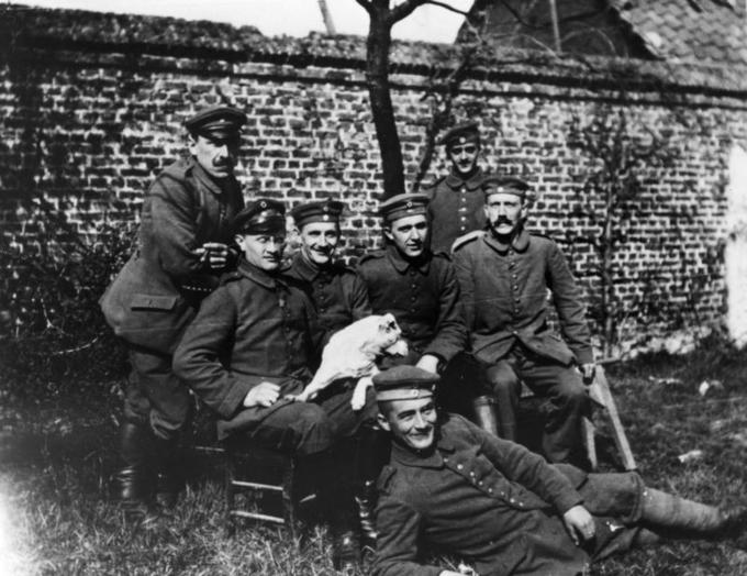 Seven men in army uniforms pose for a photo outdoors on a lawn.