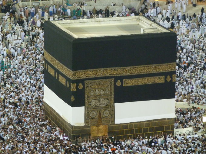A photo of the Kaaba, a black cube worshipped by Muslims, surrounded by people.
