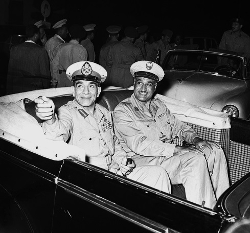Photo of Prime Minister Gamal Abdel Nasser (right) and President Muhammad Naguib (right) in an open-top automobile during celebrations marking the second anniversary of the Egyptian Revolution of 1952.