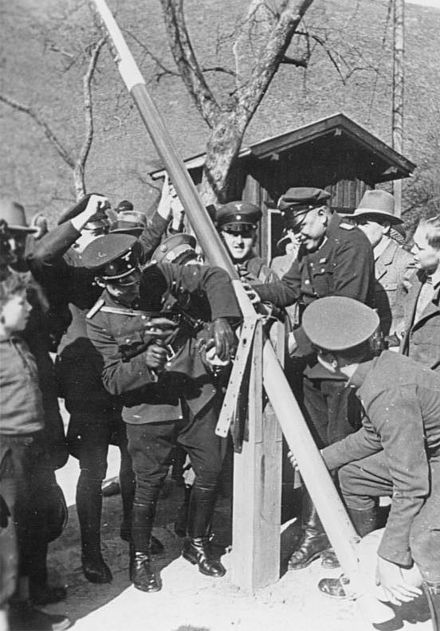 A photo of German and Austrian border police dismantle a border post in 1938.
