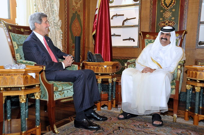 Photo of former Emir Hamad bin Khalifa Al Thani and US Secretary of State John Kerry in 2013, seated, talking with one another in a ornately decorated room.