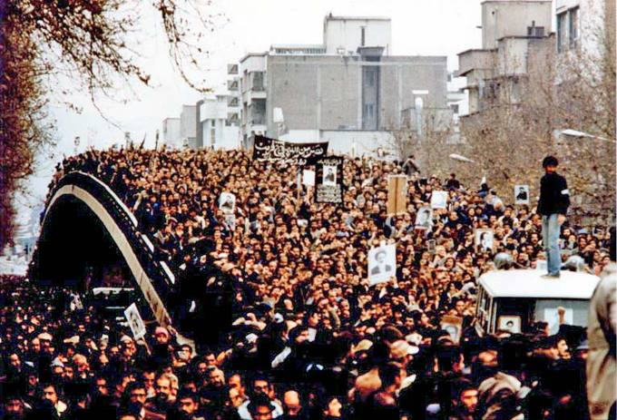 Photo of a mass demonstration in Tehran, 1979. The streets are completely filled with people, many carrying posters, and one man standing above them all on a platform.