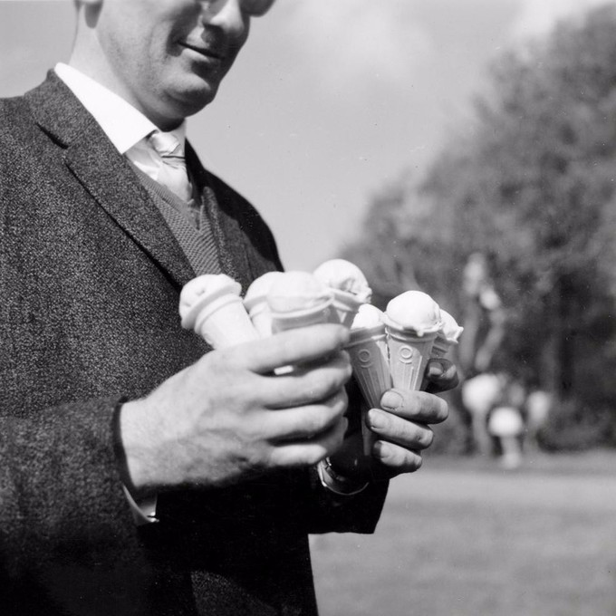 A black and white photograph of a man holding four ice cream cones in each hand.