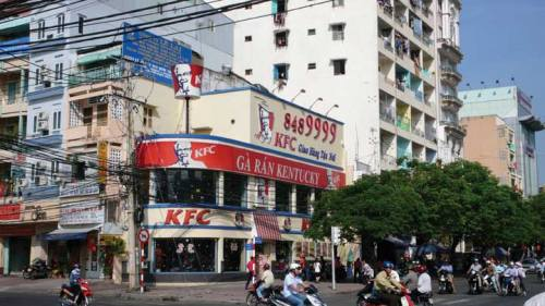 A KFC franchise in Asia. The store has at least two floors, very large windows, and very big signs.