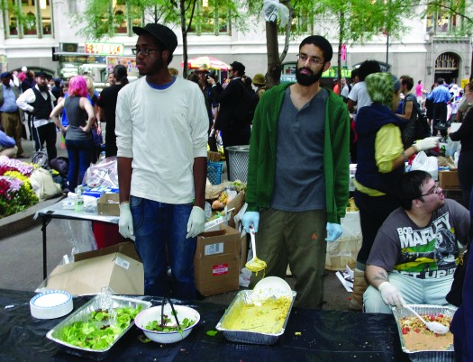 An image of three people behind a table. On the table are serval large open containers of food. A crowd of people is in the background.