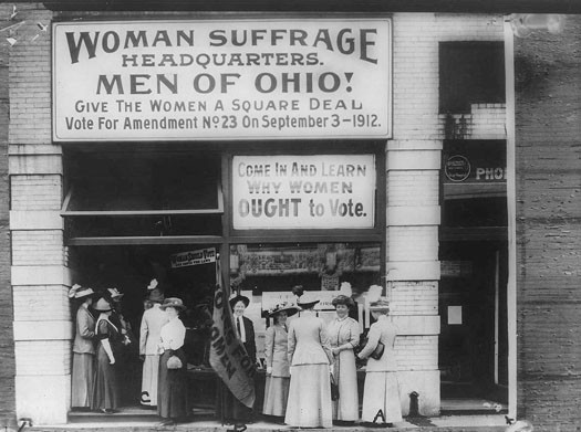 This photo shows several women outside of the Woman Suffrage Headquarters. A large sign reads