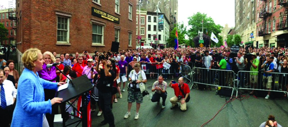 Image shows two people at a podium in front of a large crowd on a city street. One person speaks to the crowd, while the other stands next to the podium.