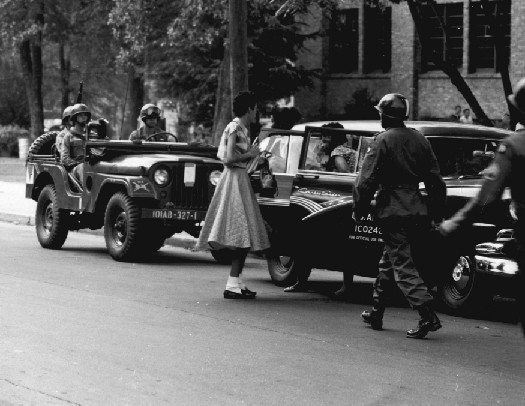 An image of several armed military officers escorting two people out of a car.