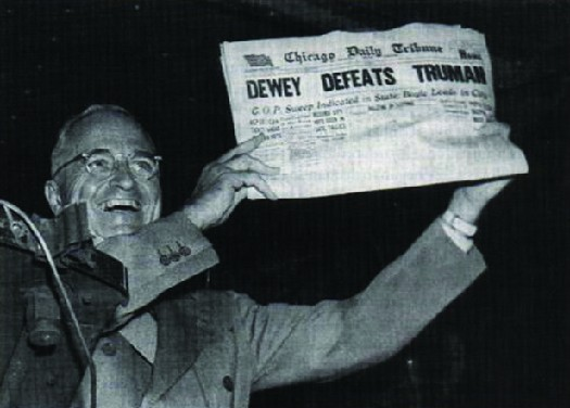 Photo shows Harry S. Truman displaying a newspaper whose headline states