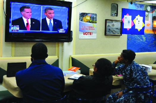 An image of three people watching a television. On the television screen are Mitt Romney and Barack Obama.