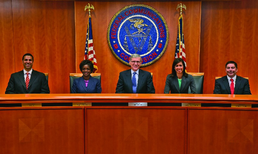 An image from left to right of Ajit Pai, Mignon Clyburn, Chairman Tom Wheeler, Jessica Rosenworcel and Michael O'Rielly seated in front of a large circular banner reading