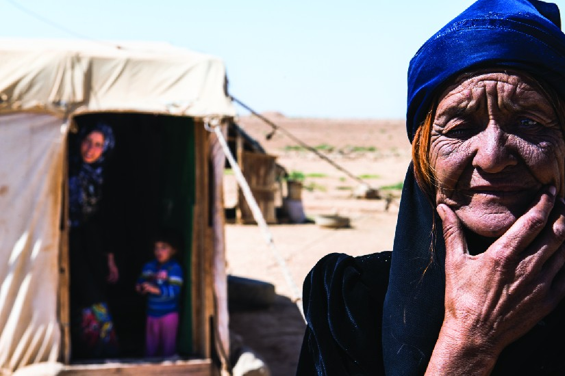 An image of an old person. In the background are an adult and a child in a tent.