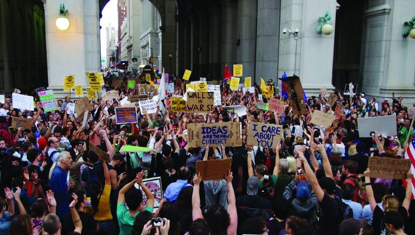 An image of a large crowd of people, several of whom are holding signs.