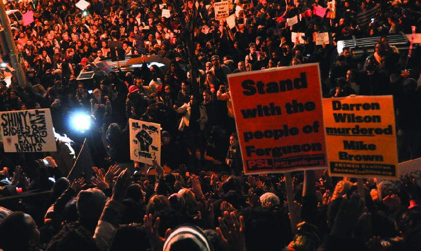An image of a large crowd of people, some holding signs that read