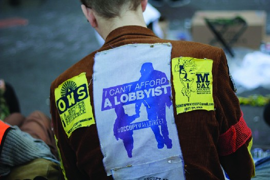 An image of the back a person wearing a jacket. A patch on the jacket reads