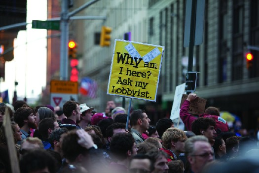 An image of a crowd of people, one of whom holds a sign that reads