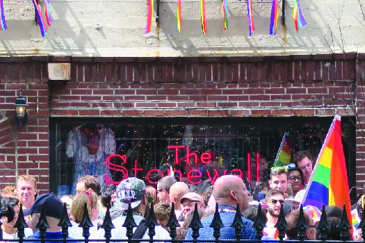 An image of a group of people standing in front of a brick building. A sign in the window of the building reads