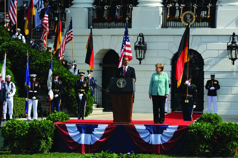 A photo of Barack Obama speaking outside the White House. Standing next to him is Angela Merkel.