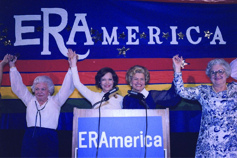 A photo of Rosalynn Carter and Betty Ford speaking at a rally in favor of the Equal Rights Amendment. Signs on stage read