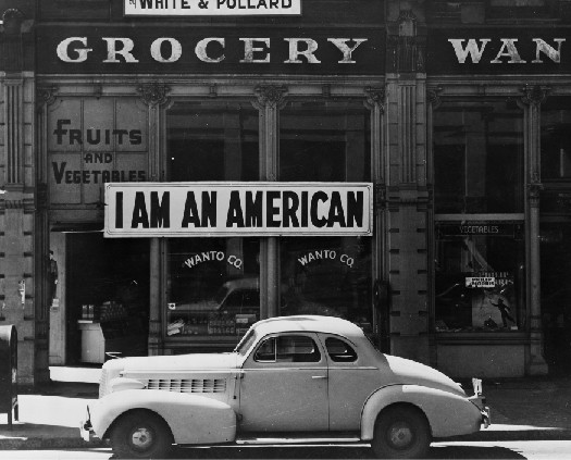 A photo of sign in a store front that says I Am An American