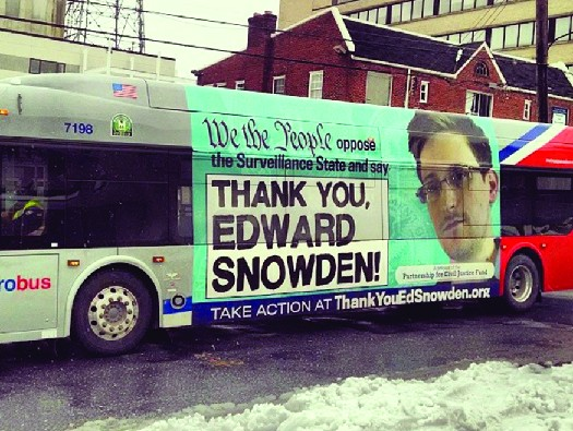 An ad on the side of a bus featuring a photo of Edward Snowden. The text says