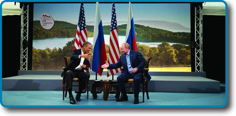 An image of Barack Obama and Vladimir Putin seated in front of two U. S. and two Russian flags, poised to shake hands.